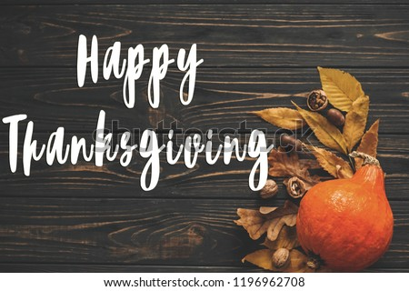 Happy Thanksgiving Text on beautiful Pumpkin with bright autumn leaves, acorns, nuts on wooden rustic table, flat lay. Seasons greeting card. Atmospheric image #1196962708