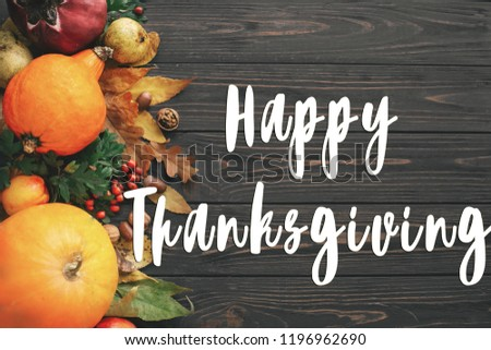 Happy Thanksgiving Text on Pumpkin, autumn vegetables with colorful leaves,acorns,nuts, berries on wooden rustic table, flat lay. Seasons greeting card #1196962690