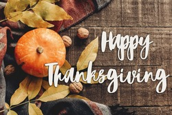 happy thanksgiving text sign  flat lay. pumpkin with leaves and walnuts on stylish scarf top view, space for text. seasonal greetings, autumn fall holidays. harvest time. cozy mood