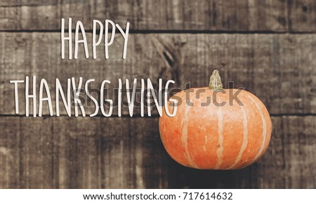 happy thanksgiving text sign, greeting card. minimalistic fall image flat lay. beautiful pumpkin on rustic wooden background, top view. cozy autumn mood. fall holiday. november celebration - Shutterstock ID 717614632