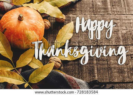 happy thanksgiving text sign on autumn pumpkin with leaves and walnuts on stylish scarf, space for text. seasonal greetings, fall holidays. harvest time. cozy mood - Shutterstock ID 728183584