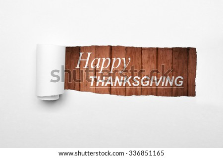 Happy thanksgiving with wooden background on the paper tear
