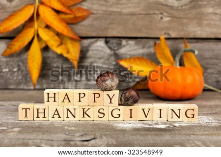 Happy Thanksgiving wooden blocks against a rustic wood background with pumpkins and autumn leaves