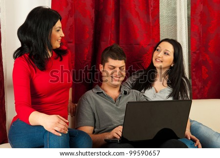 Happy three friends having conversation and using laptop in living room