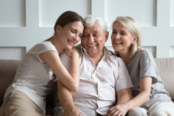 Happy three-generation family hugging sit on sofa enjoy time together at home, laughing grown up daughter with 70s dad and middle-aged 50s mom warm relations, intergenerational relative people concept