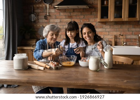 Happy three generations of Hispanic women gather in kitchen cook delicious breakfast together. Smiling little girl with young mom and mature grandmother prepare pancakes or bake at home on weekend.
