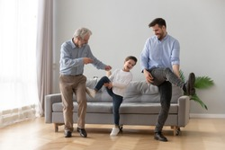 Happy three generations of men have fun dancing feel overjoyed in living room, smiling millennial father, preschooler son and grandfather entertain relaxing at home, laugh moving to rhythm together