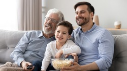 Happy three generations of men sit relax on couch have fun watching movie together eating popcorn, smiling preschooler son child spend time with dad and grandfather laugh enjoy funny cartoon on TV