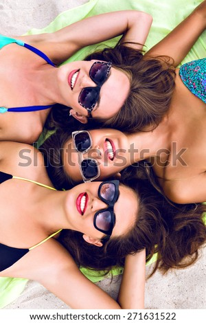 Happy three girls friends laying and getting sunbathe on the beach, close up portrait of stunning smiling women in bikini on vacation.
