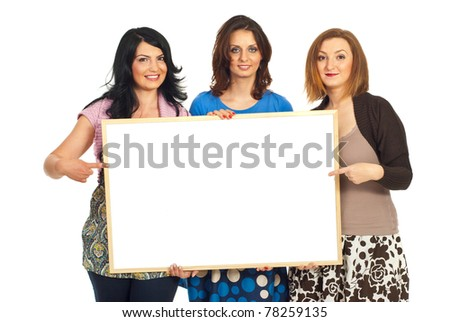 Happy three women friends holding blank banner and pointing to copy space isolated on white background