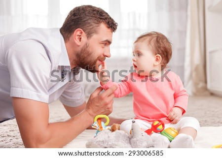 Happy time. Handsome positive father touching his baby and sitting on the floor while playing