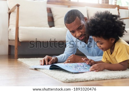Happy time of African family. African-American Father lying reading book on the floor with his son before traveling to work at living room. Parenthood and childhood concept.