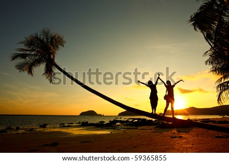 happy time two girl stand on coconut tree on the beach with sunset time Thailand Asia