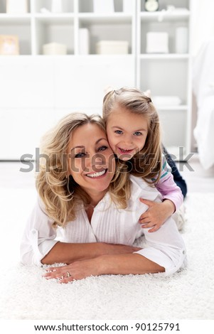 Happy times together - little girl with her beautiful mother laying on the floor