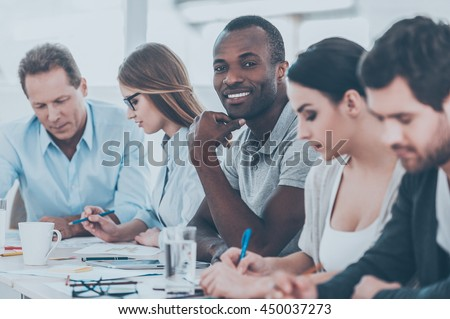 Happy to be a part of grat team. Group of business people sitting in a row at the table while handsome African man looking at camera and smiling - Shutterstock ID 450037273
