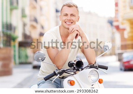 Happy to be. Happy smiling blond-haired man sitting on scooter and leaning on it
