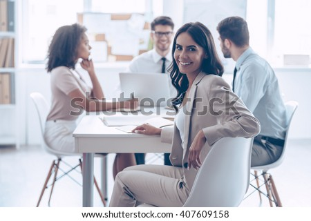 Happy to be in team. Beautiful cheerful woman looking at camera with smile while sitting at the office table with her coworkers