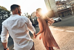 Happy to be together. Rear view of beautiful young couple holding hands and looking at each other with smile while walking through the city street
