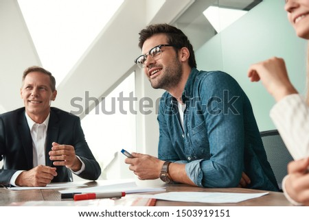 Happy to work here Young and handsome man in eyeglasses discussing something with colleagues and smiling while sitting in the modern office