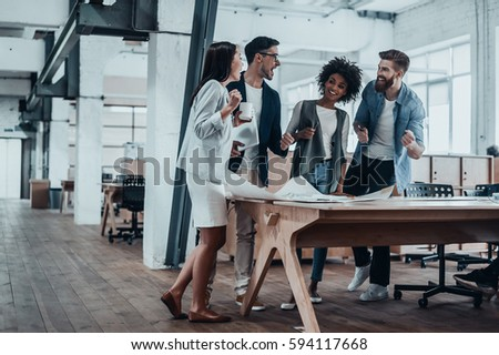 Happy to work together. Group of young business people talking and smiling while standing near the wooden desk in the office - Shutterstock ID 594117668