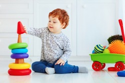 happy toddler baby boy sorting colorful rings on pyramid