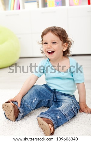 Happy toddler boy sitting on the floor laughing