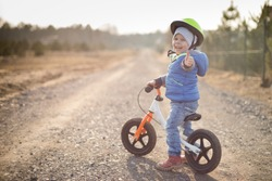 Happy toddler child boy riding on he's first bike without pedals. He's standing on road, looks back and shows thumb up.  Sport concept: kids ride bicycle; first bike; active toddler kid.