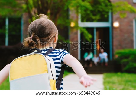 Happy Toddler girl arriving home from school with a backpack