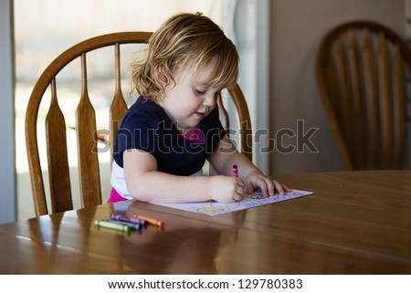 Happy toddler girl coloring