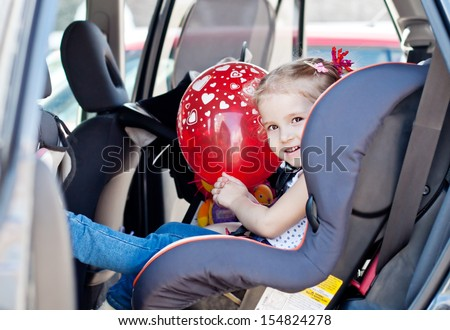 happy toddler girl in car seat  with a red balloon in hand