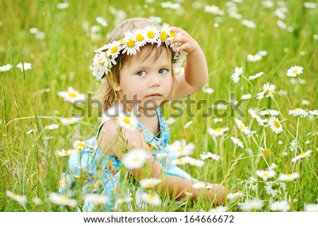 happy toddler girl on the daisy meadow