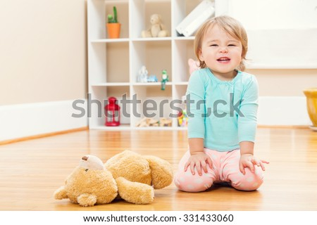 Happy toddler girl playing with a teddy bear inside her house