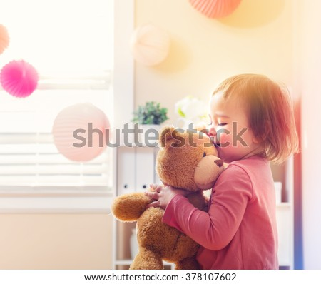 Stock Photo Happy toddler girl playing with her teddy bear at house
