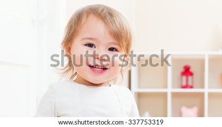Happy toddler girl with a big smile in her house