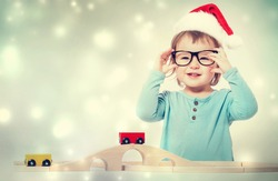 Happy toddler girl with a Santa hat and glasses playing with her toys