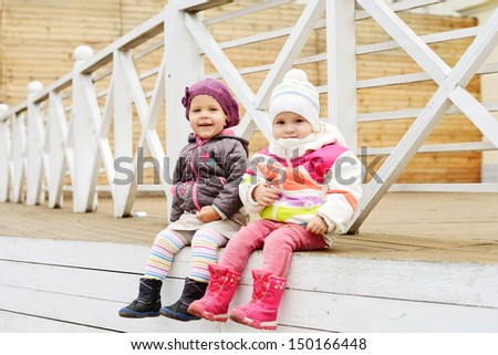 happy toddler girls sitting outdoors