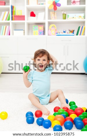 Happy toddler playing with colorful plastic balls