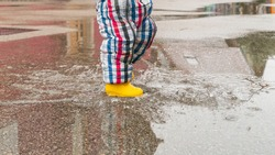 happy toddler running and jumping into pools of water in the rain, wearing yellow rubber boots. Carefree kid with colorful rain boot and suit splashing water in an urban scenery with reflections