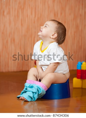 Happy toddler sitting on potty in home interior
