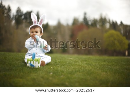 Happy toddler wearing rabbit ears trying to eat the plastic egg at the park. - stock photo
