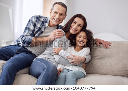 Happy together. Beautiful content curly-haired girl smiling and sitting on the couch with her parents and they hugging each other #1040777794
