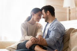 Happy together. Smiling newlyweds cuddling on couch at living room of rented purchased flat, caring husband hugging holding on knees beloved wife, young couple is glad to start new independent life