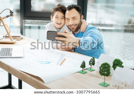 Happy together. Upbeat young man sitting at the table together with his little son and taking a selfie with him