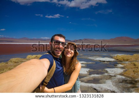 happy tourist couple backpackers take selfie photo in front of Red Lagoon or Laguna Colorada on the Altiplano near Uyuni in Bolivia at 4300 m above sea level. #1323131828