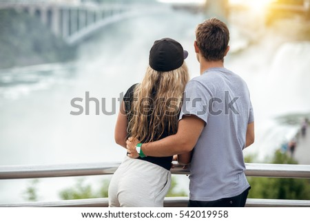 Happy tourist couple enjoying the view to Niagara Falls during romantic vacation. People looking to nature landscape at sunset time.