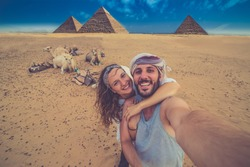 happy tourist couple on camel in Giza. holiday travel tpur near Pyramid of Khafre, Egypt