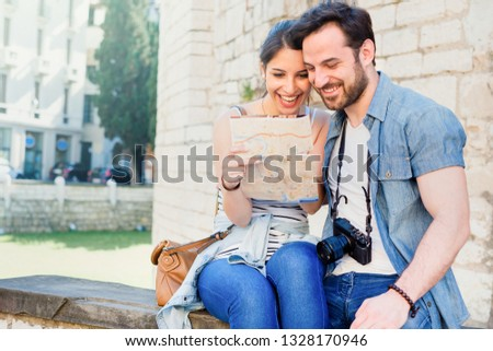 Happy tourist couple reading a map during vacation