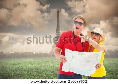 Happy tourist couple using map against paris under cloudy sky