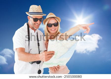Happy tourist couple using map and pointing against bright blue sky with clouds