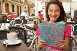 Happy tourist drinks coffee. Photo of smiling girl with map sitting at table at cafe, outside. Travel in Spain.